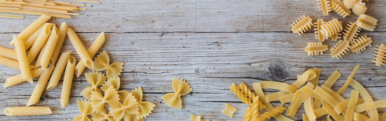 a lot of different kinds of egg noodles and yellow pasta on wooden background