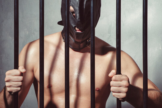 Big muscled man behind iron prison jail bars wearing a leather kinky mask #C5977
