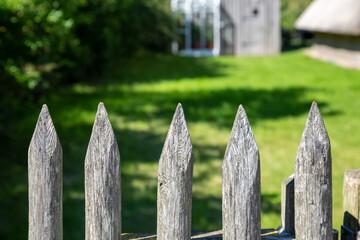 Ein Holzzaun mit Spitzen  vor einem Garten