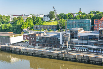 Waterfront of the Elbe river in Hamburg Altona with modern apartment and office buildings and historic harbour crane