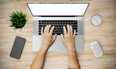 Woman's hands using laptop with blank screen on desk in home interior