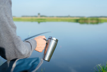Fisherman is fishing on the fishing rod and drinking a hot tea from a steel cup close up.
