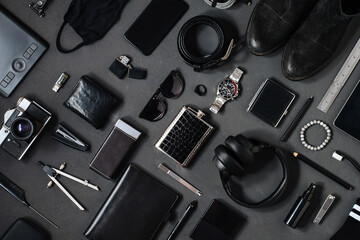 Photo topview flat lay modern style of men every day carry stuff accessories headphones camera facial mask bracelet lighter purse sunglasses tablet camera phone boots leather belt on dark background  Wall mural