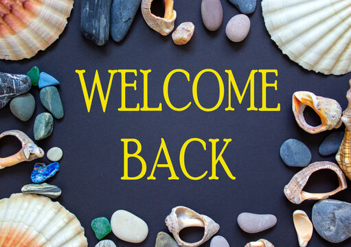 Words 'welcome back' on a beautiful black background. Sea stones and seashells. Tourism after pandemic concept.