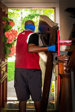Ethnic delivery man wearing mask carries detached refrigerator door out of front door of upscale house with trees in background