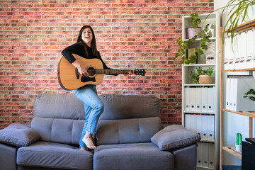 woman smiling standing on a couch playing the guitar. Behind it is a brick wall