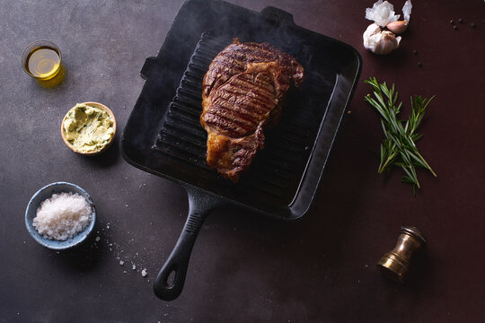 Cooked black angus prime beef ribeye steak on cast iron grilling pan with herbs, butter and spices