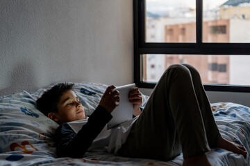 Delighted boy using tablet in bedroom during weekend