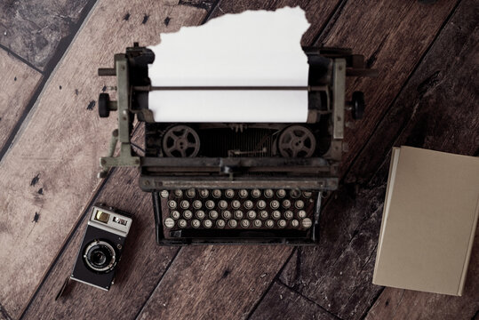 From above of old fashioned typewriter with paper placed on table with retro photo camera and notebook