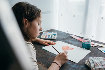 Adorable focused child sitting at table and creating painting with watercolor and paintbrush while looking at camera