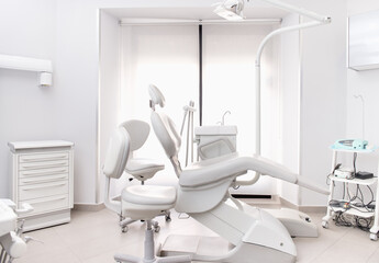 Leather dental chair with various medical instruments located in white dentist office