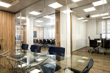 Interior of modern office with table and chairs located in room with glass walls