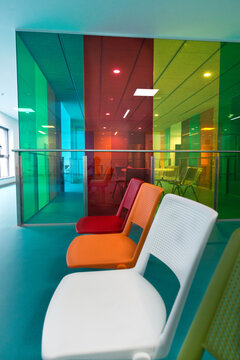 Row of bright multicolored chairs located in spacious hall of contemporary office building
