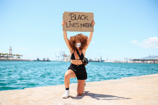 Serious ethnic female with afro hairstyle kneeling on pavement with cardboard poster with black lives matter inscription during demonstration in front of sea