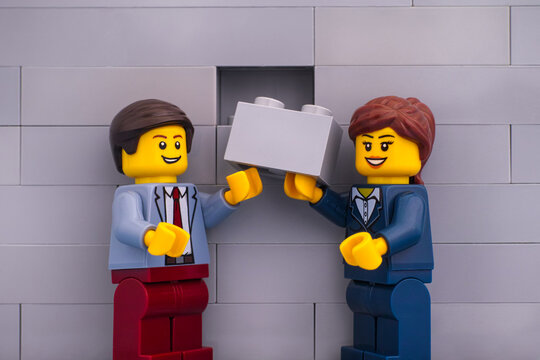 Tambov, Russian Federation - June 07, 2020 Lego businessman and businesswoman minifigures with gray brick ready to finishing building wall