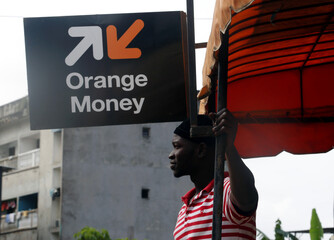 A man stands at an Orange money kiosk, as Orange launches its first Orange Bank services in Abidjan