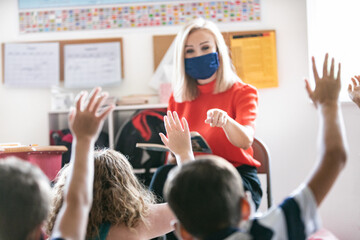 School: Teacher Wearing Face Mask And Reading Book Asks Question Of Students