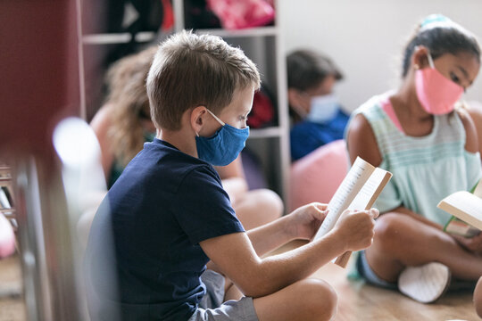School: Students Wearing Face Masks Sit On Floor For Reading Time