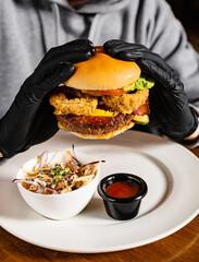 man in black gloves eating burger in the restaurant