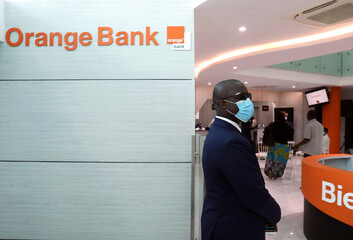A man stands inside the first Orange Bank services bulding of the French mobile operator Orange in Abidjan