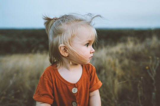 Child 1 year old girl walking outdoor cute baby blond hair family travel vacation summer season rural nature countryside