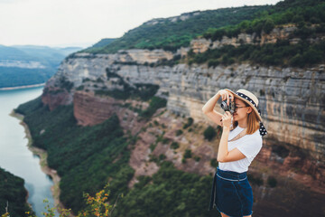 Wall Mural - young blonde girl takes picture on retro photo camera on background panorama horizin mountain and river landscape, hipster tourist enjoys hobby of photographer relax in summer nature