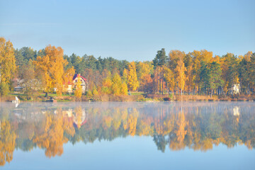 Country houses, colorful trees and a river in a morning fog, Latvia. Symmetry reflections on the water. Autumn landscape, idyllic rural scene. Environmental conservation, eco tourism theme