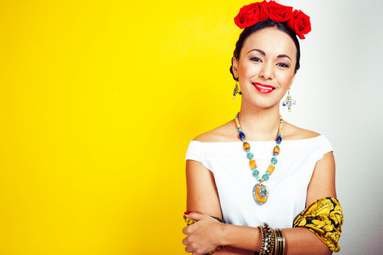 young pretty mexican woman smiling happy on yellow background, lifestyle people concept