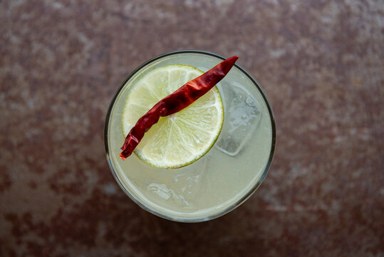 Margarita on the rocks with a chili and lemon garnish.