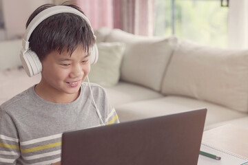 Preteen tween teen boy making facetime video calling with laptop at home, using online class...