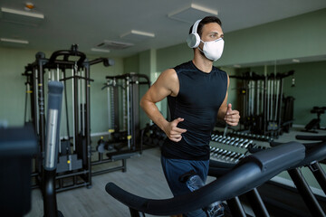 Sportsman with protective face mask running on treadmill in a gym.