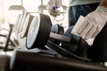 Close-up of athlete disinfecting hand weights in a gym.