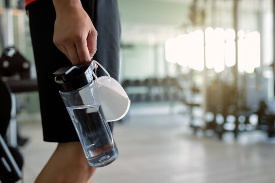 Close-up of athlete carrying protective face mask and bottle pf water in a gym.