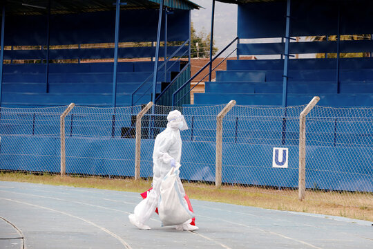 A health worker dressed in a protective suit carries bags of bio hazard materials from a field hospital builtÊon a soccer stadium in Machakos