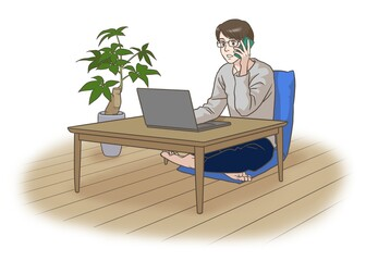 A remote working man talking on the phone in front of the laptop