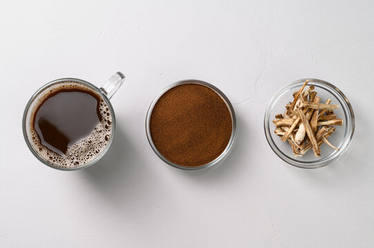 A healthy drink, an alternative to coffee. Chicory drink in a glass cup, dried roots and powder in bowls on a light gray stone background. Top view, space for text.