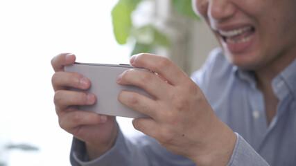 スマートフォンでゲームをしている男