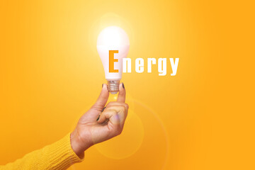 Wall Mural - hand holding light bulb with inscription energy, illuminated light bulb, image over yellow background