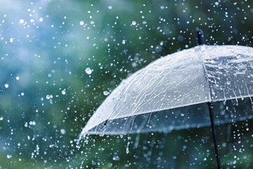 Transparent umbrella under rain against water drops splash background. Rainy weather concept.