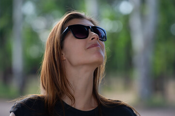 pretty girl with loose hair in sunglasses looks around.