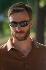 handsome bearded man in sunglasses looks around, close-up.