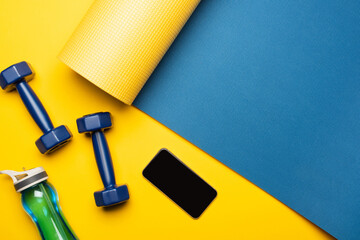 top view of blue fitness mat with dumbbells, smartphone and sports bottle on yellow background