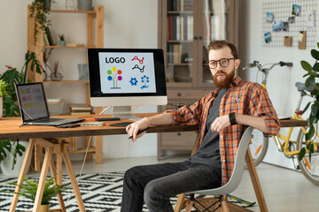 Portrait of serious handsome bearded brand designer sitting at desk with desktop computer and laptop in home office
