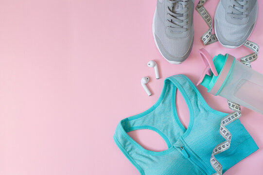 Sport equipments and clothing for woman. Flat lay of sport shoes, bottle, bra, earphones and measuring tape