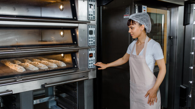 Young caucasian woman baker is looking to the bread baker proces and turn on the electic oven at baking manufacture factory.
