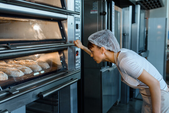 Young caucasian woman baker is looking at the bread baker process in an electric oven at a baking manufacturing factory.