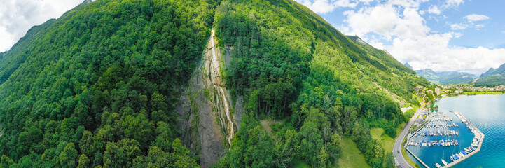 Panorama. Waterfall in the mountains near the village of Brunnen. Forest in the Alps Switzerland.