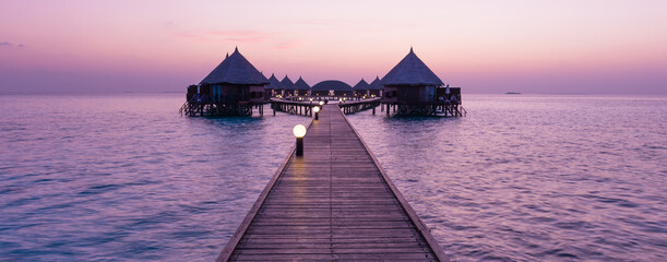 Delicate sunrise over the islands of the Maldives. Resort for relaxation. The ocean is painted with pink tones.