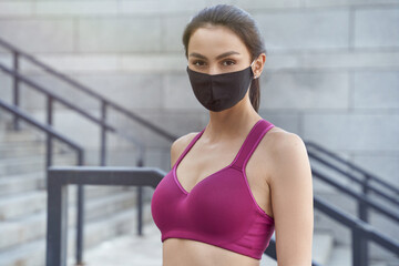 Portrait of a young caucasian fitness woman wearing protective face mask looking at camera while running outdoors during coronavirus pandemic