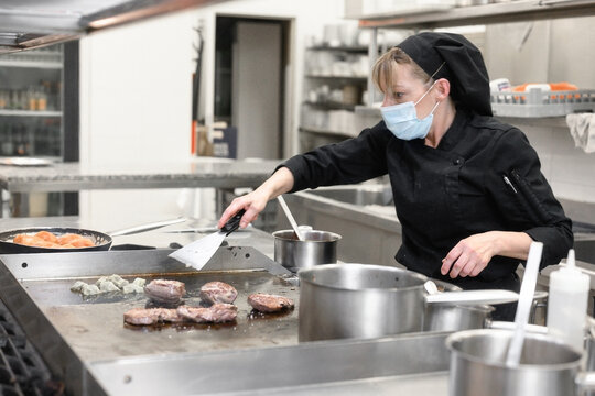 Woman Chef in protective face mask prepare food in the kitchen of a restaurant or hotel. Coronavirus prevention concept. High quality photo